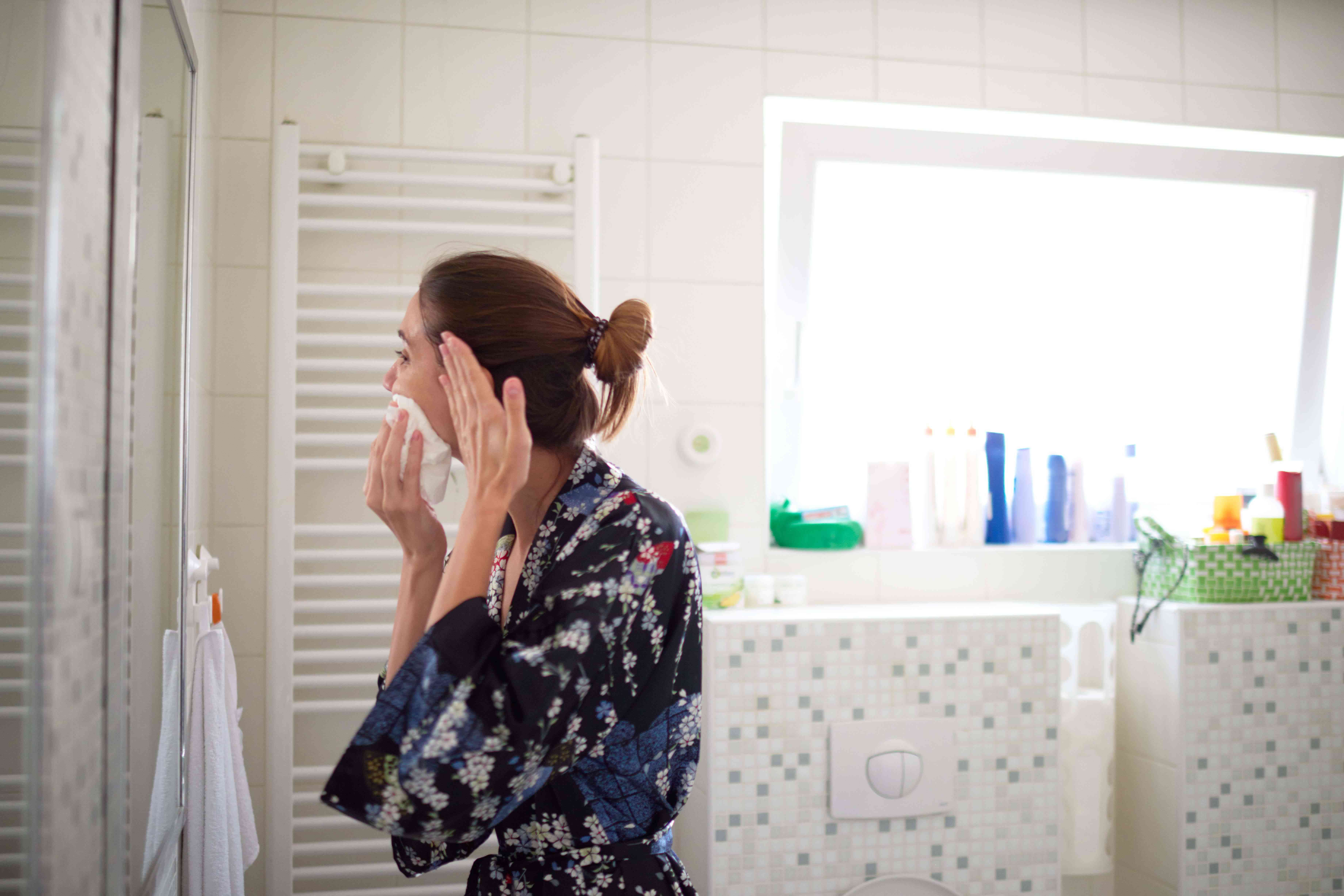 Woman in the bathroom washing her face