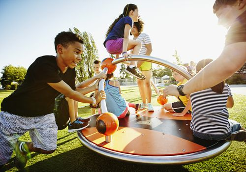 Group of kids playing on merry go round on playground