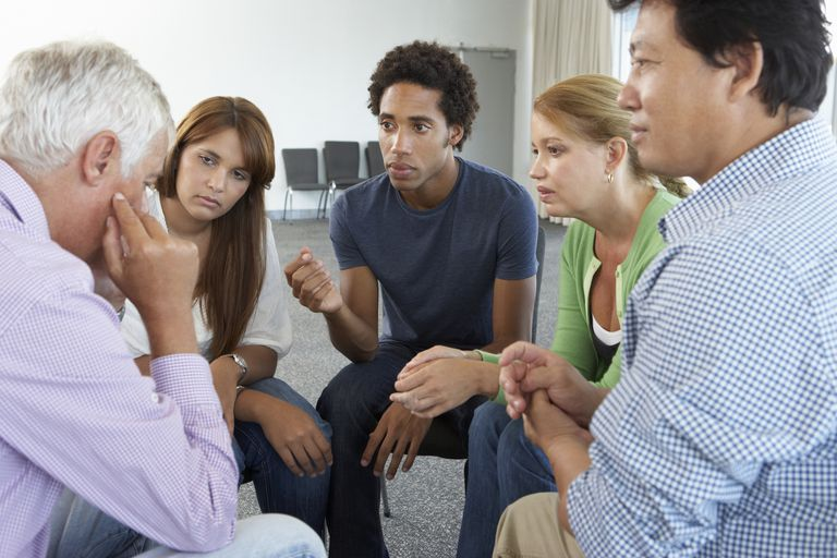 support group members sitting in a close circle and talking