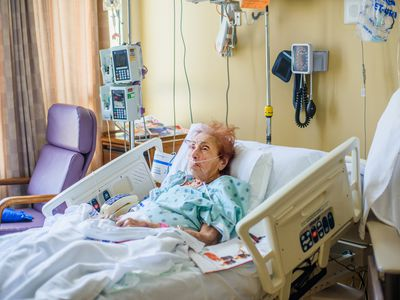Woman in a hospital bed with a feeding tube