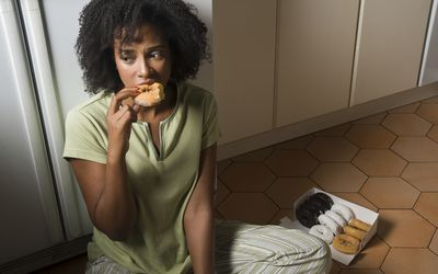A woman sits on the kitchen floor at night eating donuts.