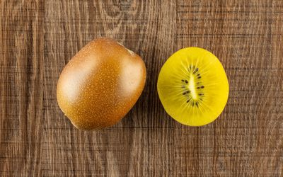 Group of one whole one half of fresh golden brown kiwi fruit sungold variety flatlay on brown wood