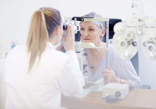 An eye doctor examining a woman's vision
