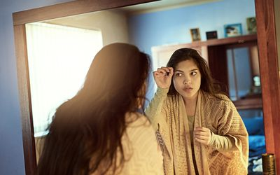 Checking hair in mirror