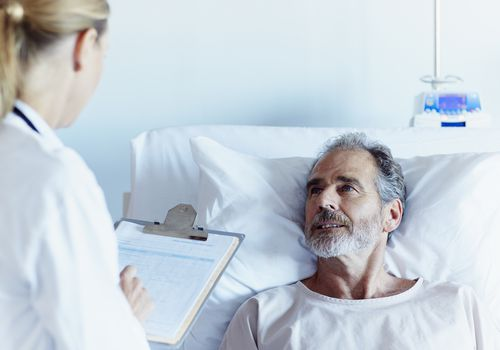 doctor and patient talking by patient's hospital bed