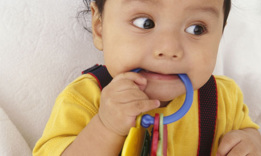 10 month old baby boy biting on teething ring