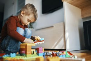 Little boy crouching on the floor at home playing with building bricks