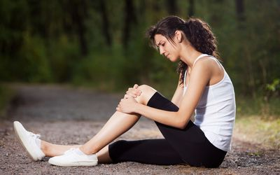 A woman sitting on the ground with knee pain