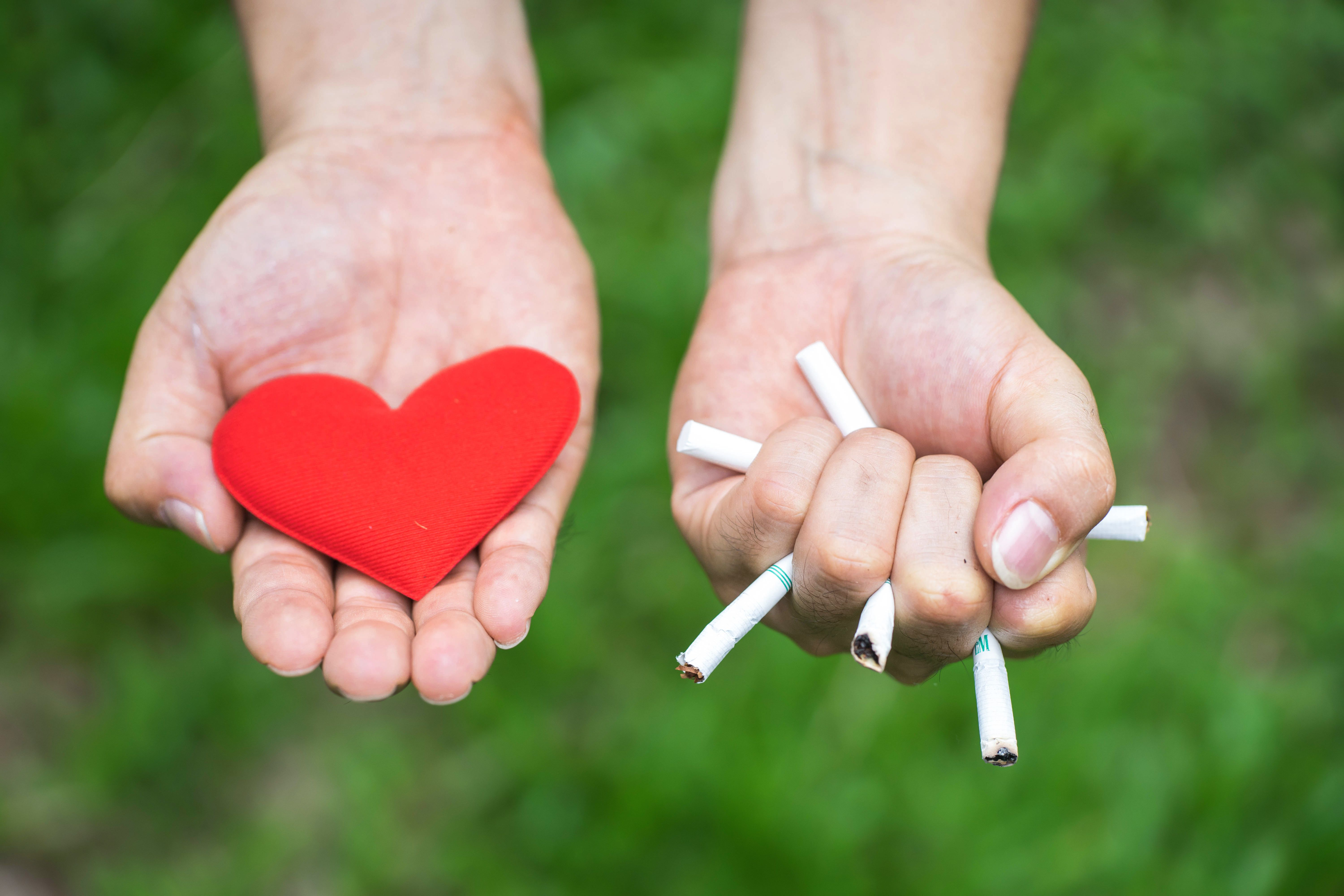 Man holding a heart in one hand and crushing cigarettes in the other
