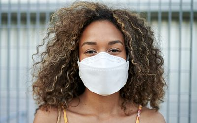 Woman wearing mask to prevent spread of COVID-19