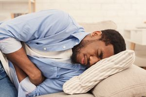 Man experiences nausea curled up on couch