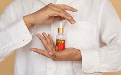 An unseen person holding a bottle of essential oil with a red ribbon in front of their chest. They are wearing a white button-down shirt.