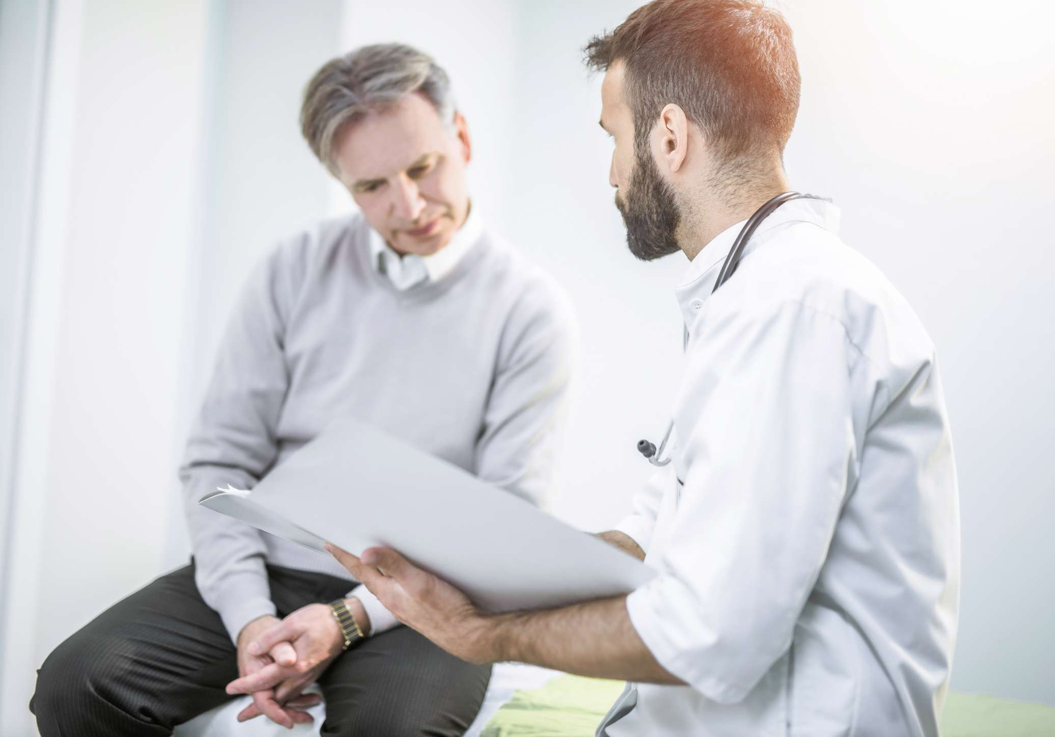 Man looking at a medical chart and talking with his doctor