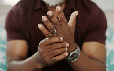 A Black man massages an arthritic hand.