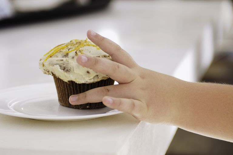 Child reaching for cupcake
