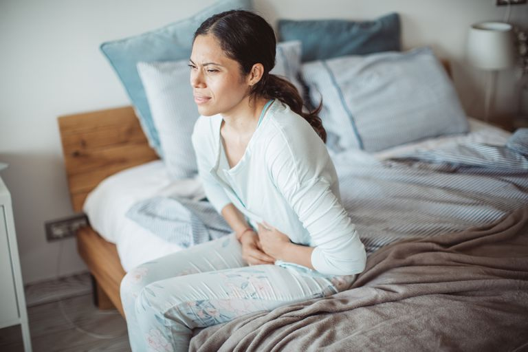 Woman with stomach ache sitting up in bed