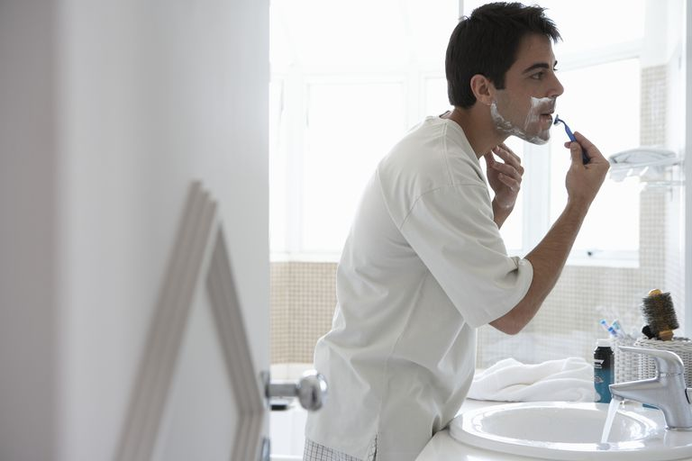 Man shaving face in bathroom mirror