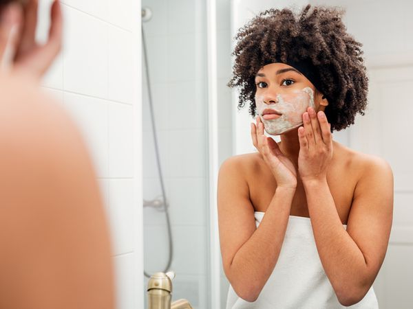 Teenage Girl Applying Facial Mask While Looking In Mirror At Bathroom - stock photo