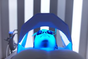 Cosmetology. Woman Face At Red Light Treatment At Beauty Clinic