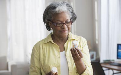 woman reading prescription bottles