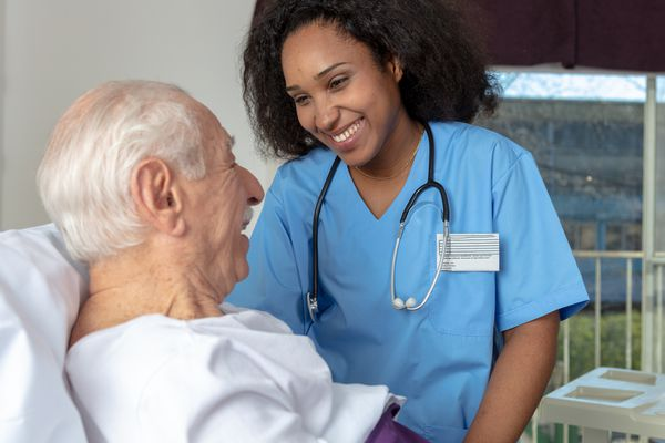 Healthcare provider smiling at the patient lying in bed