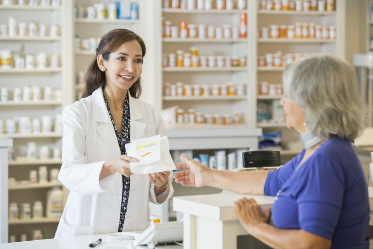 female pharmacist handing medication to senior woman