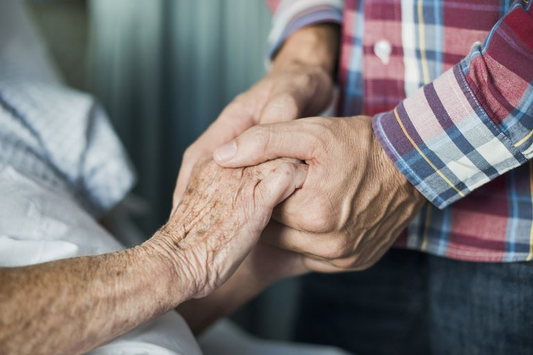 Elderly patient holding hands with someone