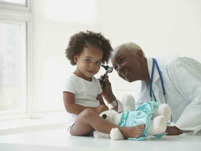 Black doctor examining girl