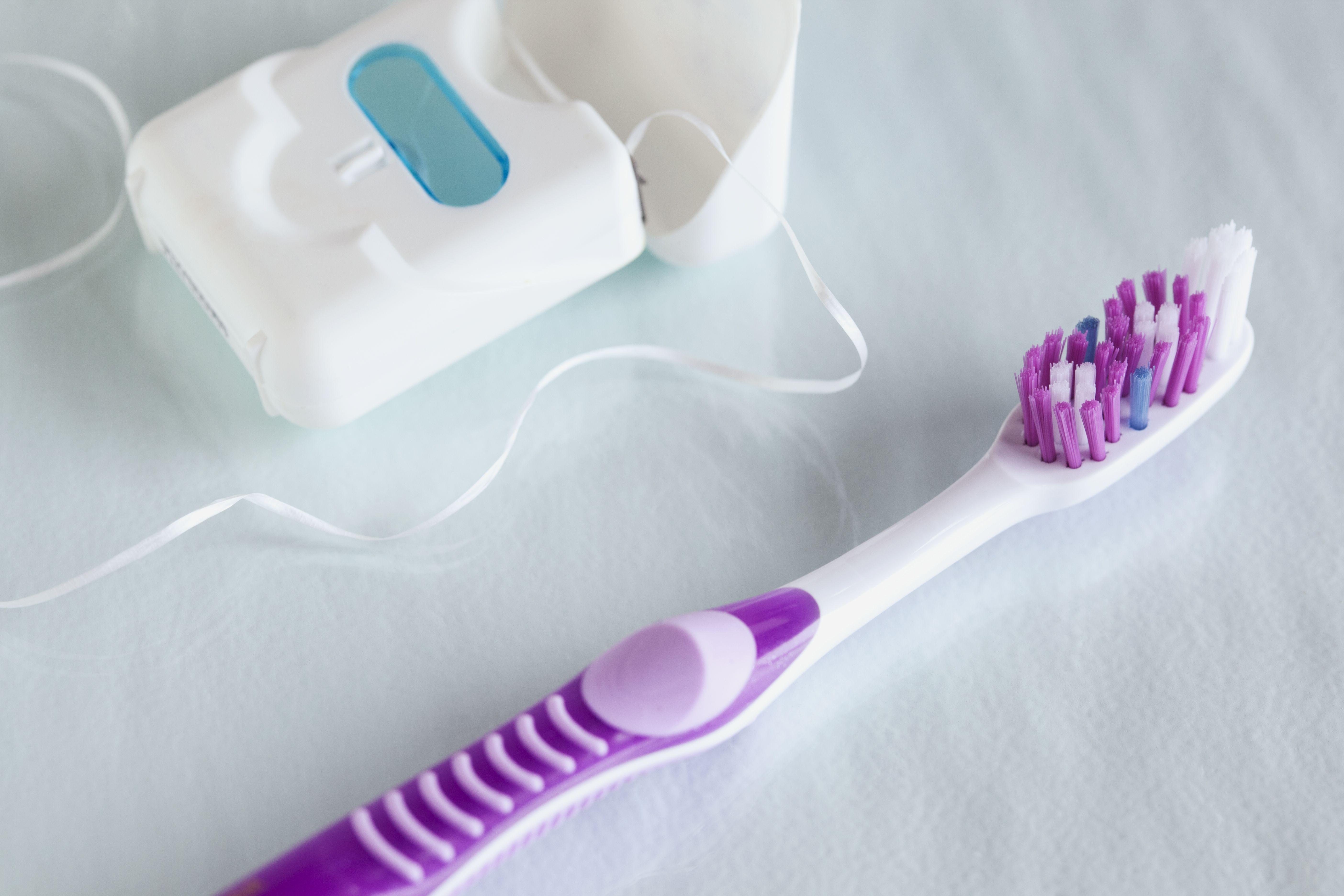 closeup of toothbrush and dental floss