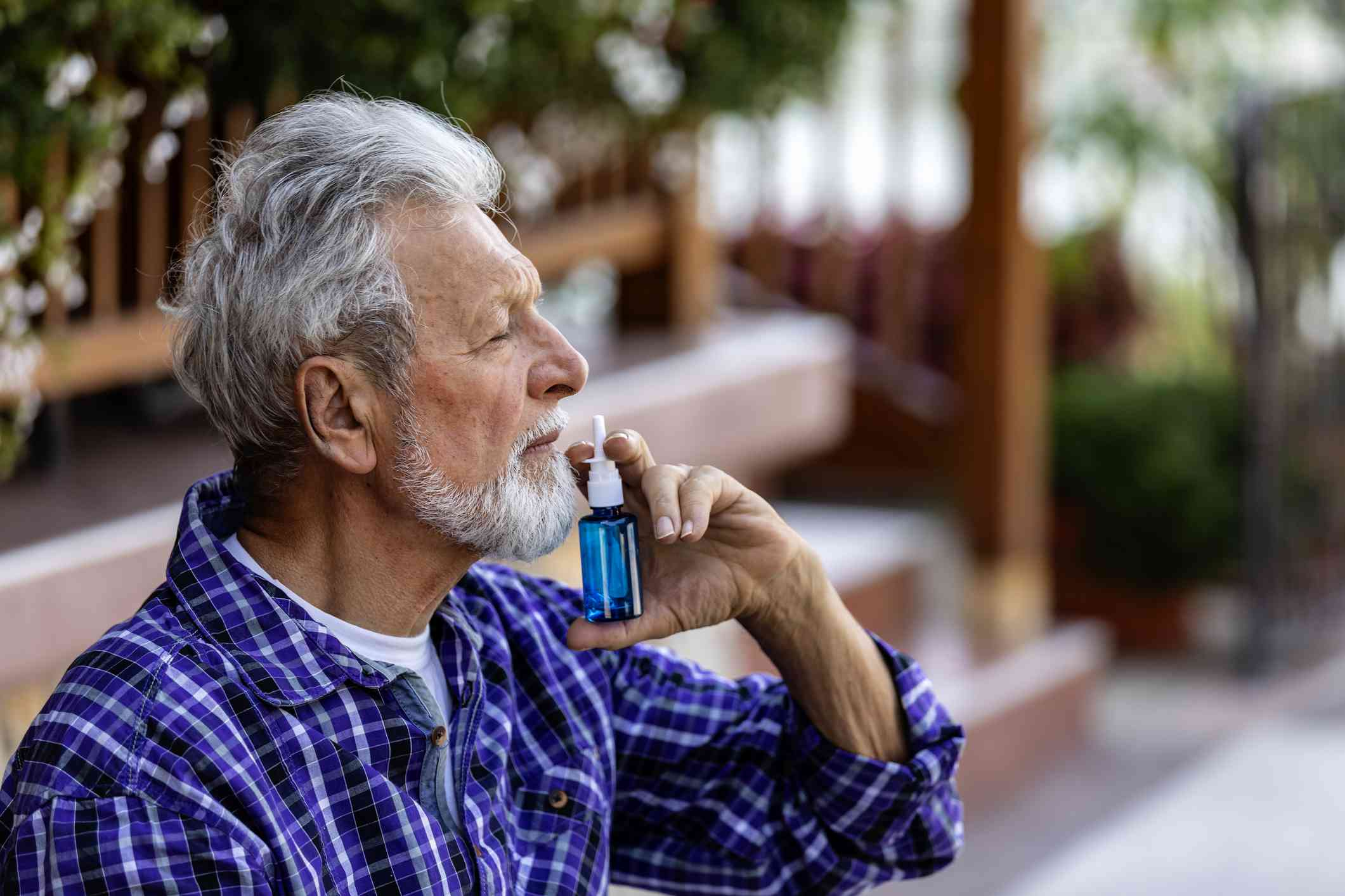 Senior Man dripping nasal drops. Portrait of senior man with a nasal spray, using nose drops, concept of treatment for allergies or the common cold