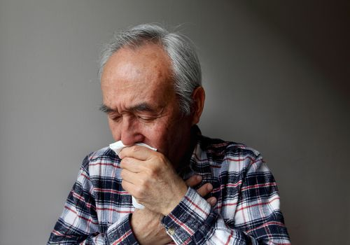 an older man coughing into a napkin