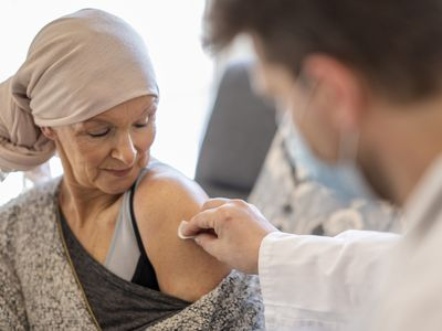 An older adult woman with a scarf on her head looking at a male healthcare worker's hand, which is cleaning a spot on her arm to deliver a vaccine.
