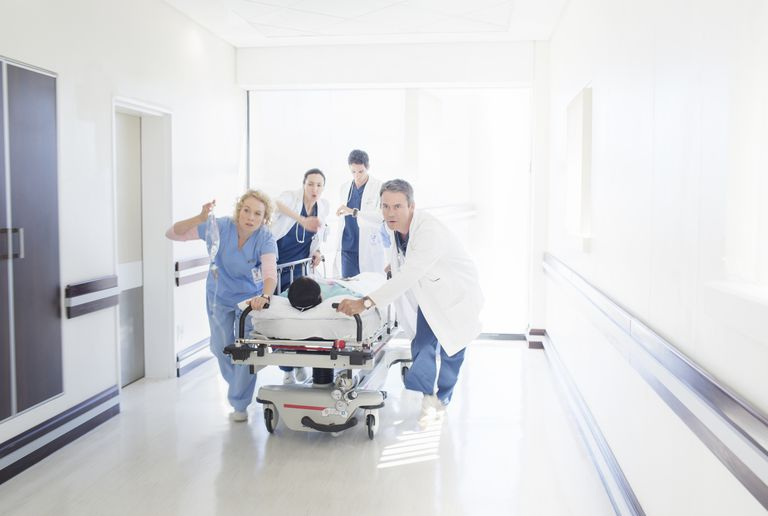 Medical team rushing down a hallway with a patient on a gurney