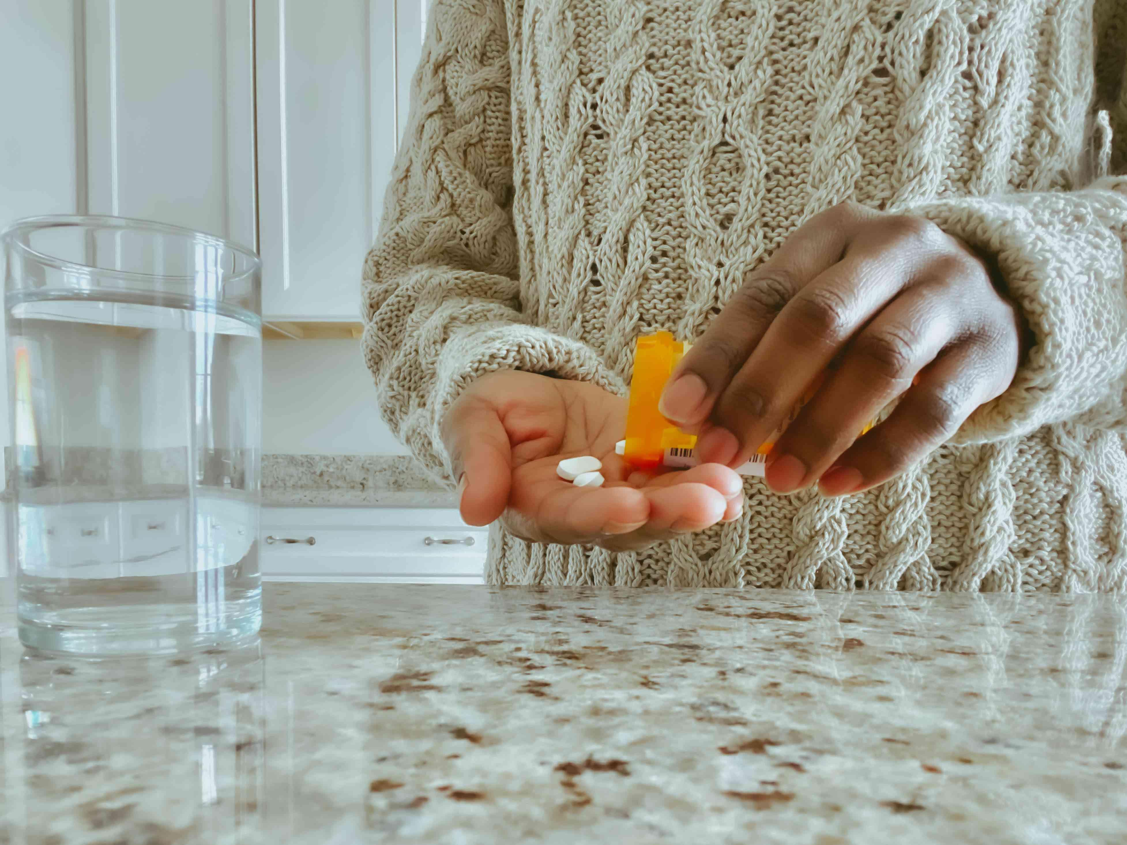 Unrecognizable Woman Pours Pills into Hand from Prescription Bottle