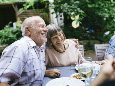 An elderly couple embracing, enjoying an outdoor meal with the family in a courtyard