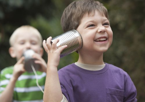Kids playing together with telephone cans