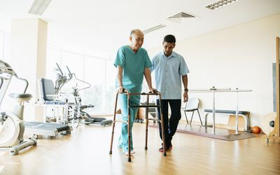 Older man in physical therapy with a walker