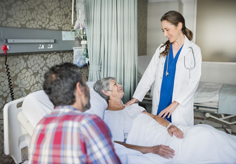 Doctor consulting senior woman in hospital bed