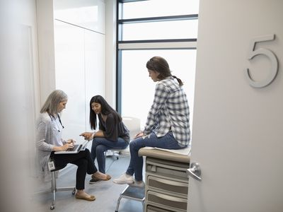 Doctor talking with a young female patient and her mother