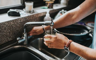 Person pouring tap water into their cup at the sink.