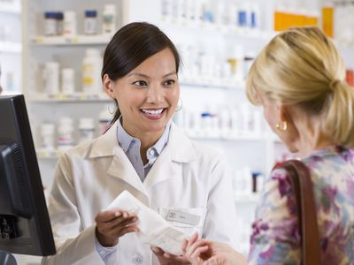 pharmacist handing prescription to a customer