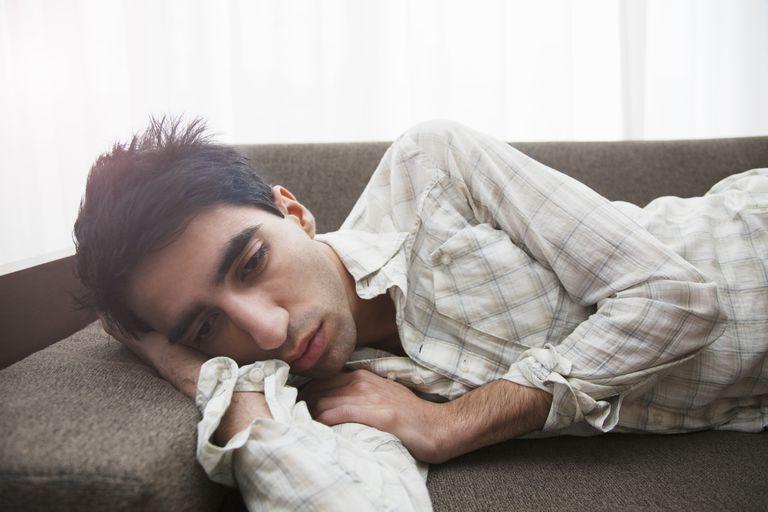 Man lying on sofa looking depressed