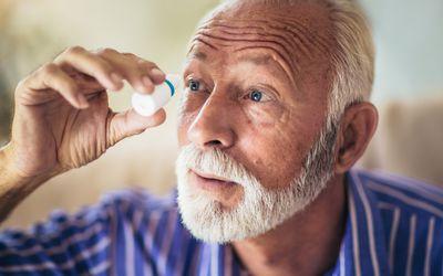 Man taking eye drops such as pilocarpine