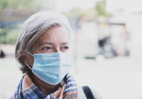 older woman wearing a surgical mask outsdie
