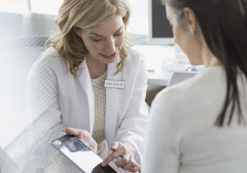 Doctor talking with a woman and pointing out something on a tablet