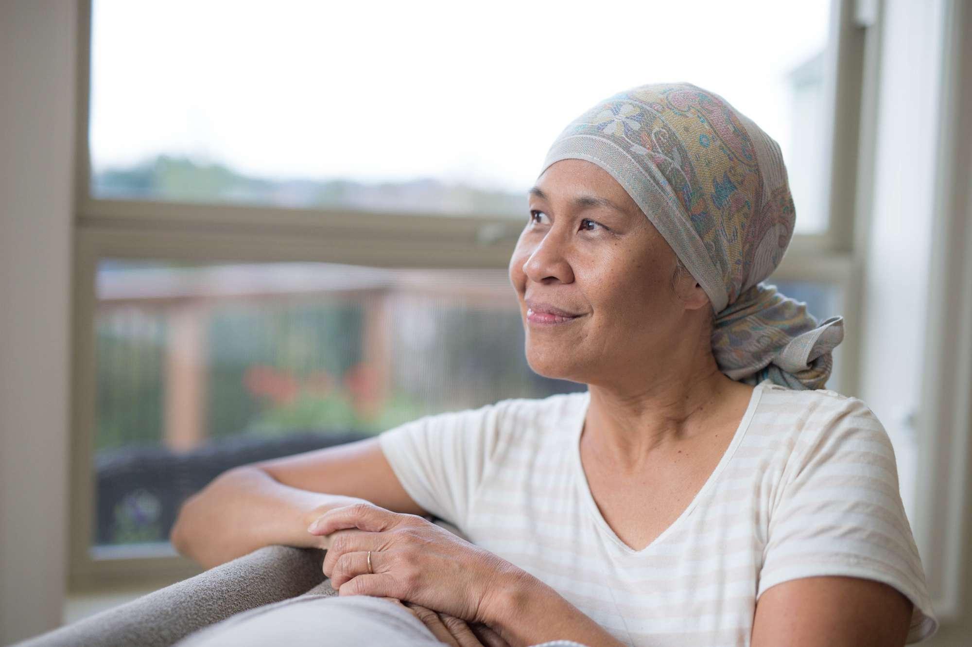 Woman in head wrap looking outside the window