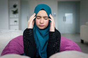 Girl in hijab squeezes eyes shut and holds hands to either side of her head