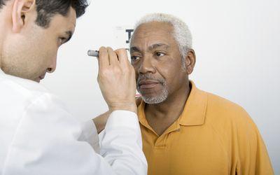 Mid adult doctor examines senior man's eyesight