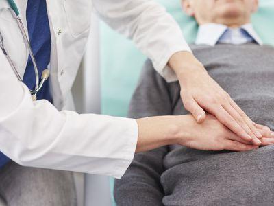 Close up of doctor examining stomach of senior man