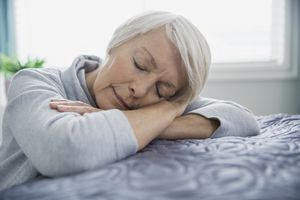 Tired woman lying on the bed fro a small nap